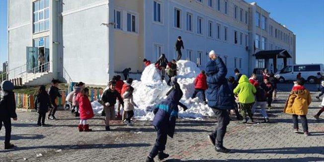 Öğrenciler okul bahçesine taşınan karla sevindi