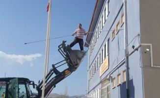 Okul müdürü, kepçenin kovasına binip okulu boyadı